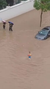 Read more about the article Moment Boy Swims Along Flooded Wuhan Street In Rubber Ring And Trunks